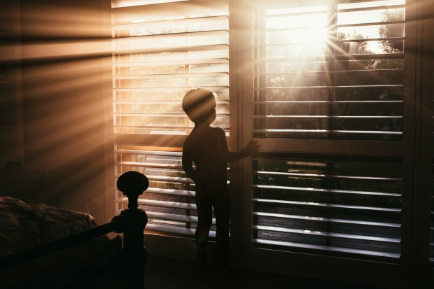 photo-of-boy-looking-out-a-window-with-streaks-of-light-coming-through-the-blinds-by-Amy-Shire